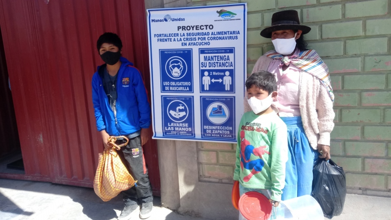En Ayacucho (Perú), una familia indígena recibe alimentos junto a un cartel con las medidas de precaución (Perú - Asociación Cuencas Andinas Kiswar)